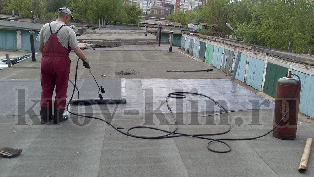 Укладка второго слоя кровли гидроизоляционного материала на крышу гаража